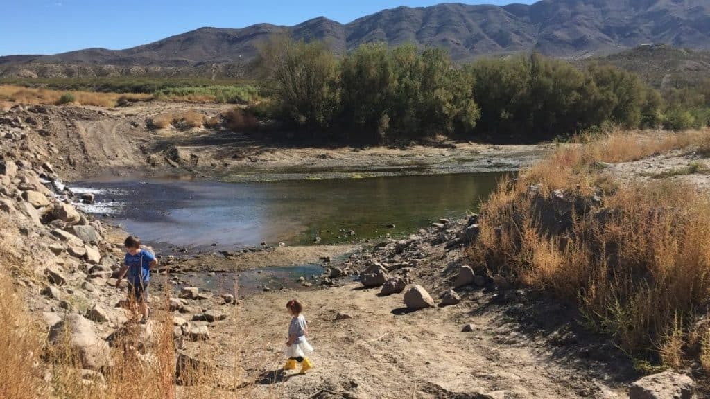 June Jewell's little boy and girl playing on the banks of the Rio Grande near the temporary dam in Truth or Consequences