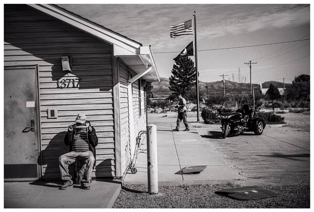 Man eating corn on the cob at the Post Office, Arrey, New Mexico