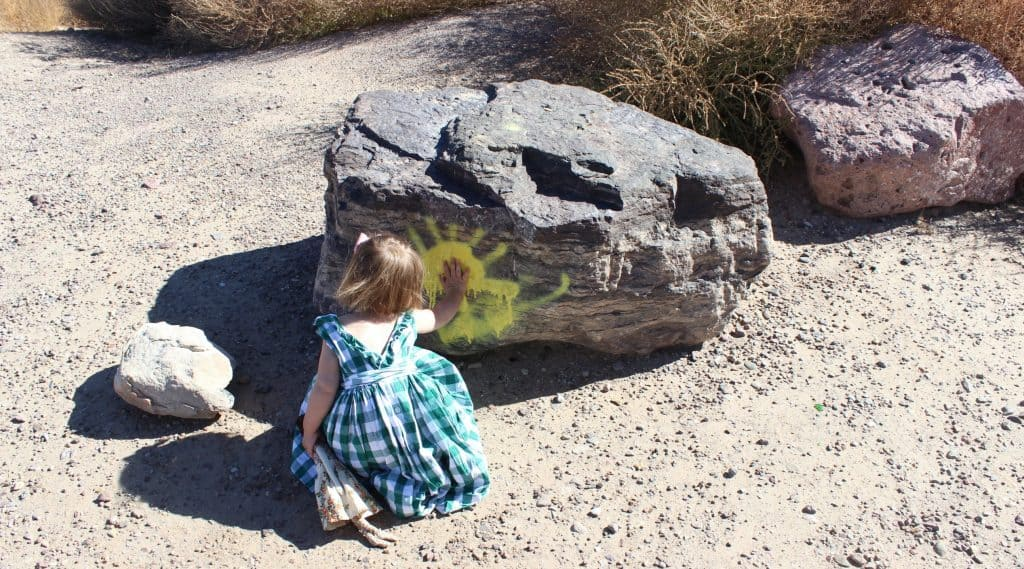 Daisy Russett touching a rock painted with a sun